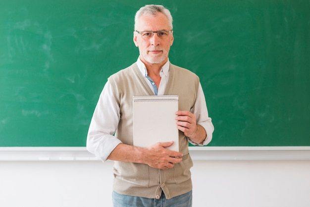 Senior mâle, professeur, tenue, cahier, debout, contre, tableau noir