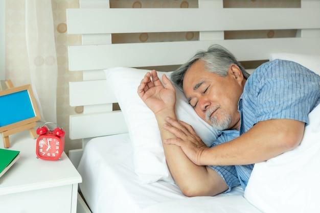 Senior male, vieil homme dormant sur l'oreiller sur un lit blanc le matin - concept de bonne santé masculin senior de mode de vie