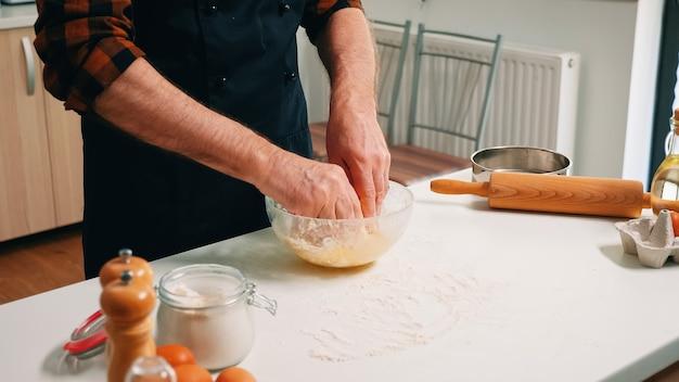 Senior man baker pétrir la pâte à pain dans un bol en verre. chef âgé à la retraite avec saupoudrage uniforme, tamisage, tamisage des ingrédients bruts à la main et mélange avec de la farine pour la cuisson de pizzas maison, biscuits.