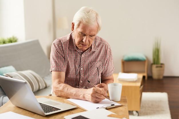 Senior man counting budget à la maison