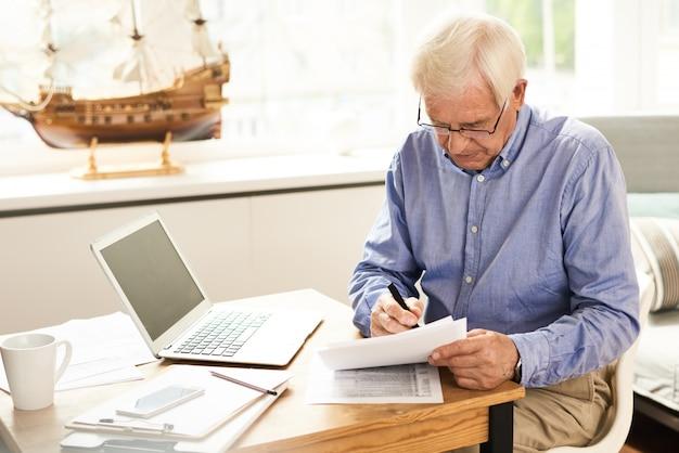Senior man dépôt du rapport d'impôt