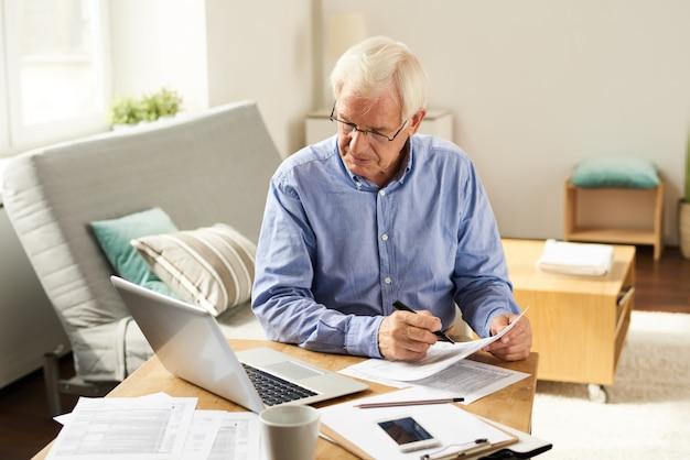 Senior man dépôt d'un rapport d'impôt à la maison