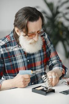 Senior man avec équipement pour la soudure. travailler à la maison.