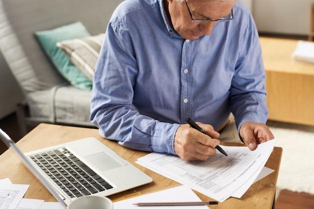 Senior man filling application form à la maison