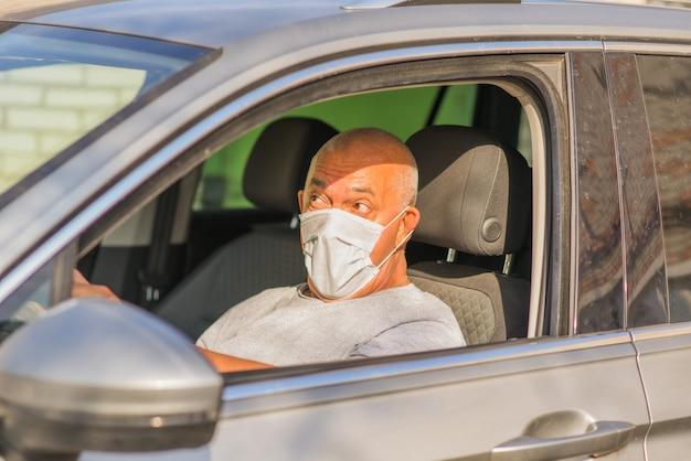 Senior man in masque médical conduisant une voiture. concept de coronavirus. protection respiratoire