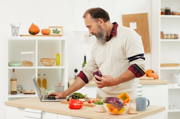 Senior man watching cooking instructions