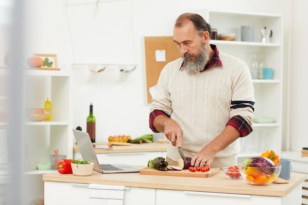 Senior man watching cooking tutorial