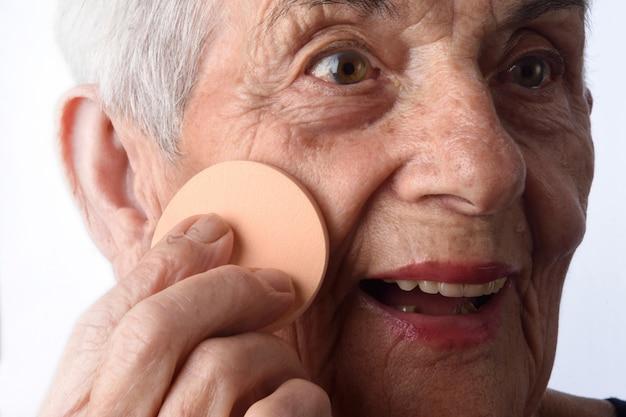 Senior maquillage femme visage sur fond blanc