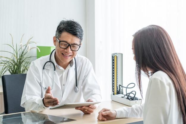 Senior médecin asiatique et patient discutent