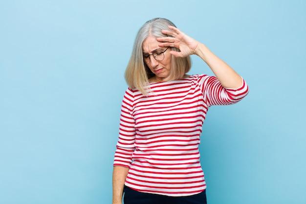 Senior ou moyen âge jolie femme à la stress, fatiguée et frustrée, séchant la sueur du front, se sentant désespérée et épuisée