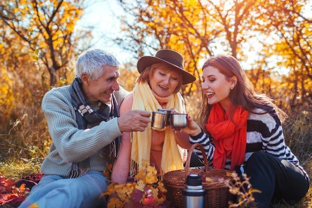 Senior parents buvant du thé dans la forêt d'automne avec leur fille