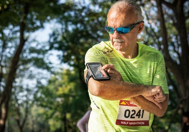 Senior runner utilisant une application de tracker de fitness
