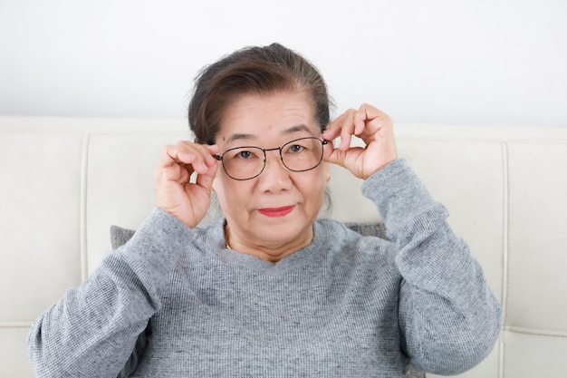 Senior senior asiatique dans le salon lifestyle visage heureux