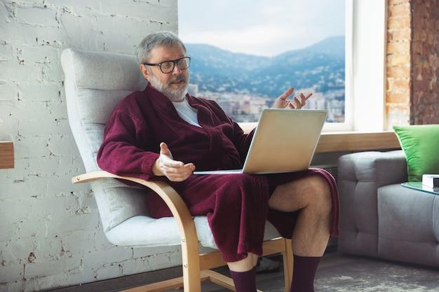 Senior senior homme âgé pendant la quarantaine, se rendant compte de l'importance de rester à la maison pendant l'épidémie de virus