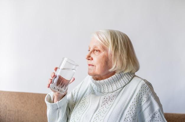 Senior senior tenant un verre d'eau