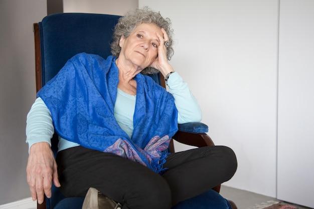 Senior songeuse dame assise dans le fauteuil à bascule et regardant ailleurs
