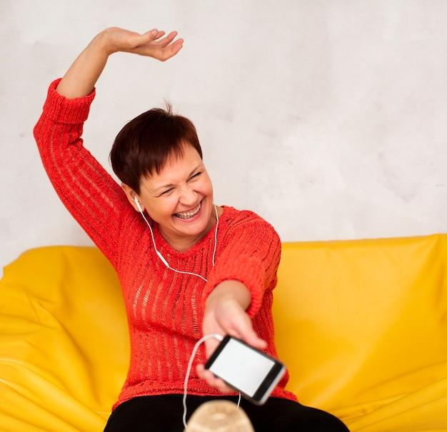 Senior souriant femme écoutant de la musique