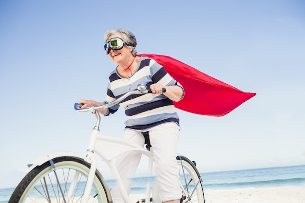 Senior superwoman sur un vélo
