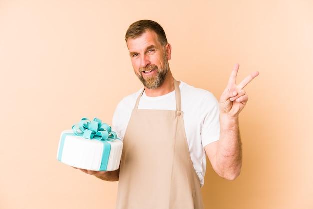 Senior tenant un gâteau isolé sur beige joyeux et insouciant montrant un symbole de paix avec les doigts.