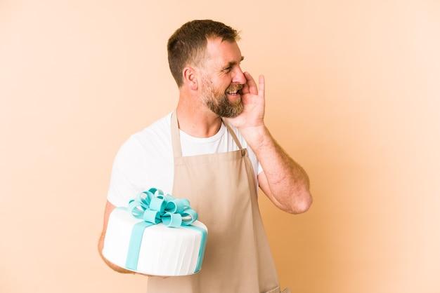 Senior tenant un gâteau isolé sur un mur beige criant et tenant la paume près de la bouche ouverte.