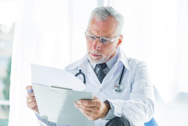 Senior thérapeute examinant des dossiers