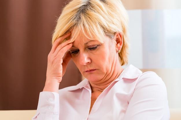 Senior touchant le front ayant des maux de tête ou des douleurs