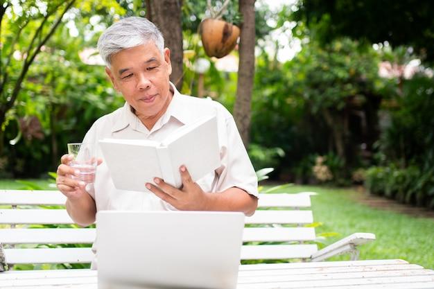 Senior vieil homme lisant un livre dans le parc et de l'eau potable.