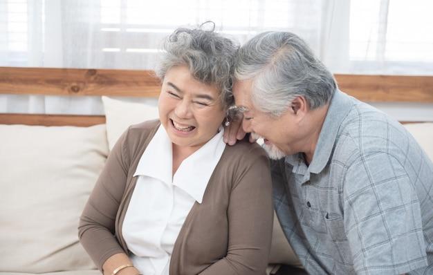 Senior vieux couple asiatique rire assis sur le canapé à la maison.