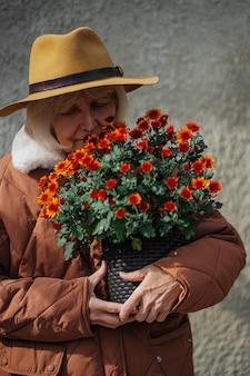Senior woman apprécie le parfum des fleurs. femme âgée en vêtements d'extérieur à la mode et chapeau portant un pot