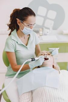 Senior woman ayant un traitement dentaire au cabinet du dentiste. une femme est traitée pour les dents