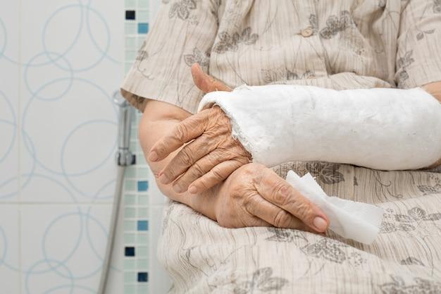 Senior woman avec bras cassé à l'aide des toilettes avec déambulateur.