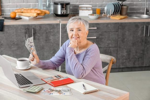Senior woman compter de l'argent à la maison