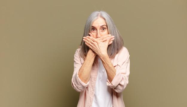 Senior woman couvrant la bouche avec les mains avec une expression choquée et surprise