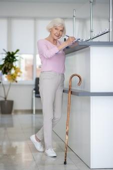 Senior woman debout à la réception et à la réflexion