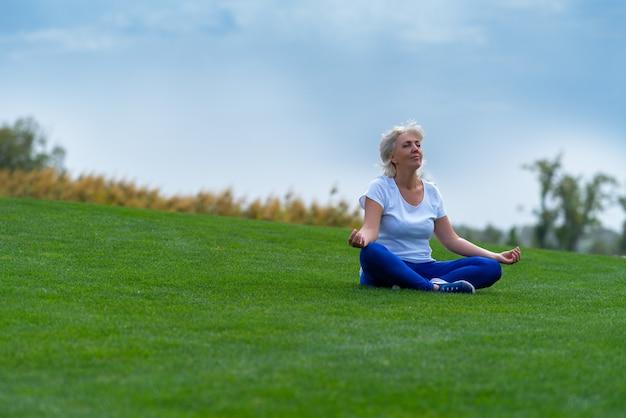 Senior woman détente sur l'herbe verte pendant la méditation