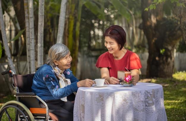 Senior woman détente avec sa fille dans la cour.