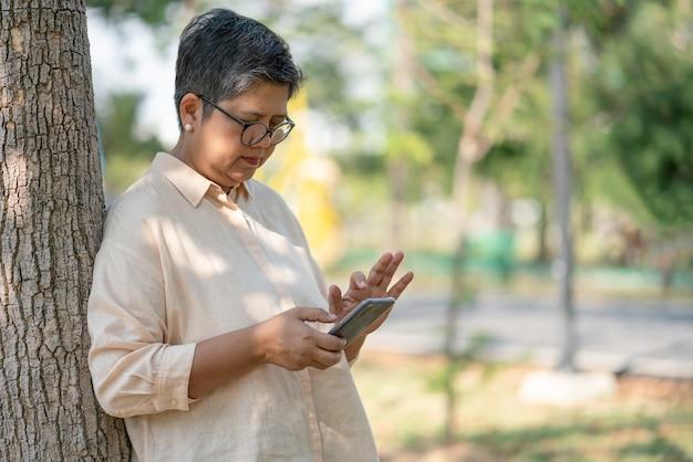 Senior woman détente tout en regardant le smartphone dans le parc