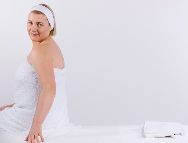 Senior woman, enveloppé dans une serviette blanche, est assis sur une table de massage avant la procédure et a l'air mignon à la caméra.