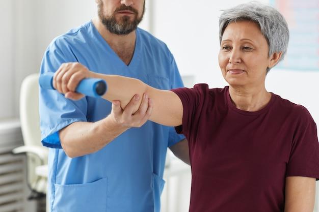 Senior woman étirant sa main et s'entraîner avec des haltères avec un médecin debout à proximité et l'aider à l'hôpital