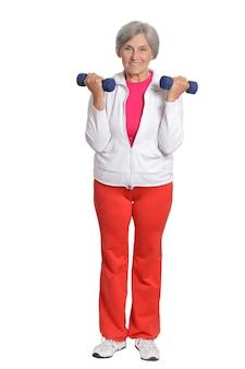 Senior woman exerçant avec des haltères sur fond blanc