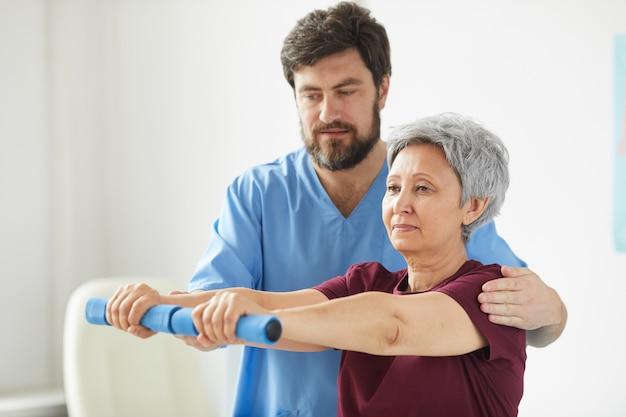 Senior woman exercice avec haltères et médecin de sexe masculin l'aidant