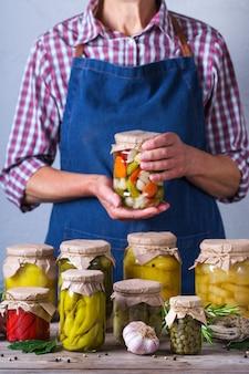 Senior woman holding in hands pot avec des aliments conservés et fermentés faits maison. variété de légumes marinés et marinés. entretien ménager, économie domestique, préservation des récoltes
