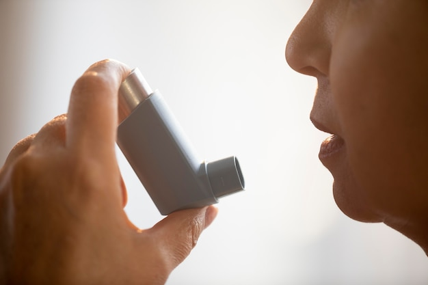 Senior woman holding inhalateur d'asthme