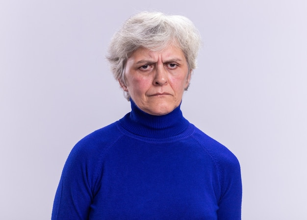 Senior woman in blue col roulé regardant la caméra avec un visage sérieux fronçant les sourcils debout sur blanc
