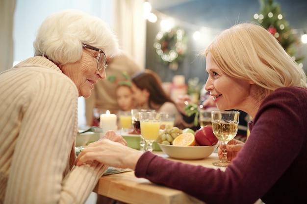 Senior woman in eyeglasses et sa fille blonde bavardant par table de fête servie pendant le dîner en famille