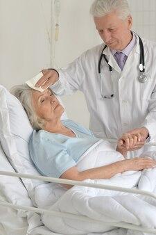 Senior woman in hospital avec des médecins attentionnés