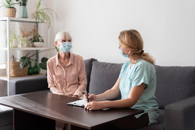 Senior woman in maison de soins infirmiers avec infirmière pendant le contrôle