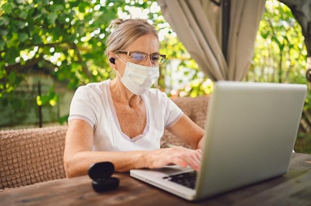Senior woman in masque de protection à l'aide d'un ordinateur portable