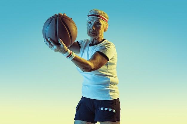 Senior woman in sportwear jouant au basket sur fond dégradé, néon. le modèle féminin en grande forme reste actif. concept de sport, activité, mouvement, bien-être, confiance. copyspace.