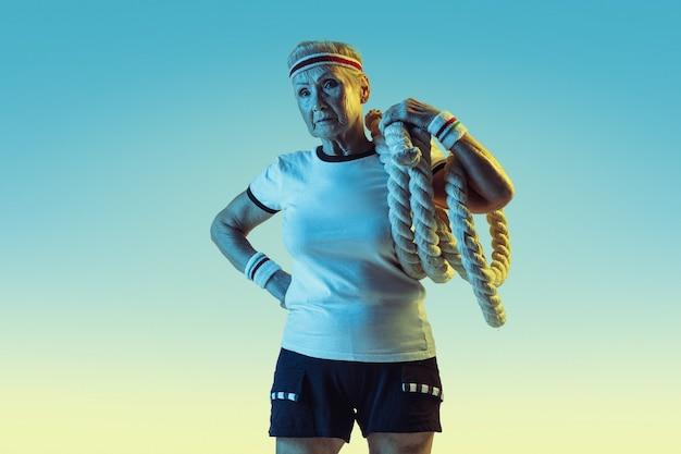 Senior woman in sportwear training avec des cordes sur fond dégradé, néon.